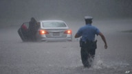 A Philadelphia police officer rushes to help a stranded motorist during Tropical Storm Isaias, Tuesday, Aug. 4, 2020, in…
