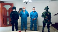 In this photo released by Colombia's Prosecutor's Press Office, a police officer and a soldier flank Mark Grennon, second left,…