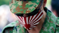 A visitor wearing a protective mask to help curb the spread of the coronavirus pays respects to the war dead at Yasukuni Shrine…