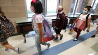 File---File picture taken Aug.5, 2020 shows pupils wearing masks to prevent the spread of COVID19 walking to class to begin…