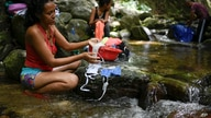A woman washes her protective face masks with runoff water from the Avila mountain in Caracas, Venezuela, Sunday, June 21, 2020…