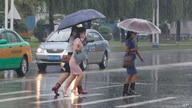Women walk with umbrellas during torrential rains, Wednesday, August 5, 2020, in Pyongyang. North Korea says torrential rains…