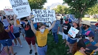 Protesters hold signs outside the Cottonwood Heights Police Department on Monday, Aug. 3, 2020, in Cottonwood Heights, Utah…