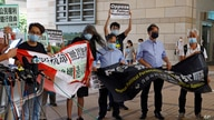 Pro-democracy activists including Leung Kwok-hung, second left, hold banners outside a district court in Hong Kong, Thursday,…