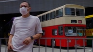 Occupy Central leader Benny Tai stands in front of a vintage double-deck bus used as a polling center for voting in Hong Kong…