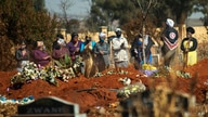 Mourners pray during a burial ceremony at the Olifantsveil Cemetery outside Johannesburg, South Africa, Thursday Aug. 6, 2020…