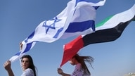 Israeli model May Tager, left, holds Israel's blue-and-white flag bearing the Star of David while next to her Anastasia…