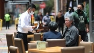 A waiter wearing a mask to curb the spread of the new coronavirus tends to a couple of customers outside a restaurant in the…