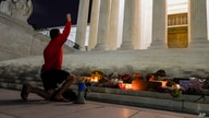 A man kneels in front of a memorial of candles and flowers outside the Supreme Court Friday, Sept. 18, 2020, in Washington,…