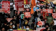 Protesters march as they hold a rally at the University of the Philippines against the 5th State of the Nation Address (SONA)…