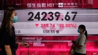 People wearing face masks walk past a bank's electronic board showing the Hong Kong share index at Hong Kong Stock Exchange…