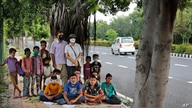 A former diplomat Virendra Gupta and his singer wife Veena Gupta pose for a photograph with underprivileged children whom they…
