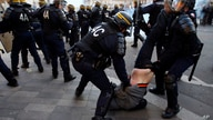FILE - In this Saturday, Feb. 18, 2017 file photo riot Police officers apprehend a protester during clashes at a demonstration…