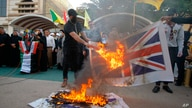 Supporters of the Iran-backed Kataeb Hezbollah militia burn representations of Israeli, U.S. and British flags during a protest…