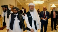 Deputy Head of Political Office of the Taliban Abdul Salam Hanafi, center, heads to attend the opening session of the peace…