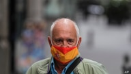 A man wearing a face mask to prevent the spread of coronavirus decorated with the Spanish flag stands in a street in downtown…