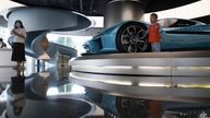 A child pose for photos near a race car displayed at the NIO flagship store in Beijing on Thursday, Aug. 20, 2020. The chairman…