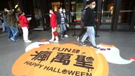 People wear face masks to protect against the spread of the coronavirus as they walk through a shopping district in Taipei,…