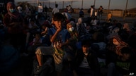 Refugees and migrants wait to board buses after their arrival at the port of Lavrio, about 75 kilometers (48miles) south of…
