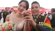Lesbian couple Yi Wang, right, and Yumi Meng show their wedding rings during a military mass weddings ceremony in Taoyuan city,…