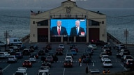 People watch from their vehicles as President Donald Trump, on left of video screen, and Democratic presidential candidate…