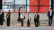 People stand by an electronic stock board of a securities firm in Tokyo, Monday, Oct. 19, 2020. Shares advanced in Asia on…