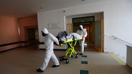 Health care workers transport a COVID-19 patient from an intensive care unit (ICU) at a hospital in Kyjov to a hospital in Brno…