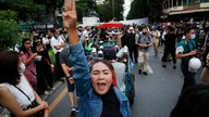 Pro-democracy demonstrators flash a three-finger salute of defiance during a protest rally in the Silom business district of…