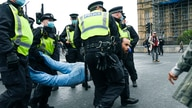 Police detain a man, during a coronavirus anti-lockdown protest on Westminster Bridge, in London, Saturday, Oct. 24, 2020. (AP…