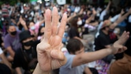 Pro-democracy activists flash three-fingered salutes outside remand prison, in which some of the activists are kept in Bangkok,…