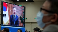 Chinese Foreign Minister Wang Yi, centre, and attendees wearing face masks to help curb the spread of the coronavirus listen to…