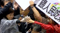 In this image made from video, Taiwanese Premier Su Tseng-chang holds a microphone as opposition party lawmakers from the…