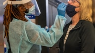 Traveler Patty Siegel, right, from Los Angeles gets a COVID-19 nasal swab test before a planned trip to Hawaii at the Los…