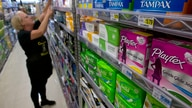 FILE - In this June 22, 2016 file photo, Tammy Compton restocks tampons at Compton's Market, in Sacramento, Calif. Gov. Jerry…