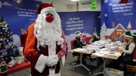 "A postal worker dressed as Santa, talks with co-workers who call themselves ""Elves"" as they open envelopes addressed to ""Pere…"