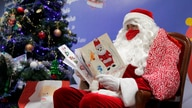 "FILE - In this Monday, Nov. 23, 2020 file photo, a postal worker dressed as Santa, reads letters to addressed to ""Pere Noel"" -…"