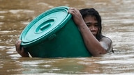 A resident uses a plastic container as a floater while negotiating rising floodwaters in Marikina, Philippines due to Typhoon…