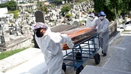 Cemetery workers carry the coffin of Genivaldo Santos, who died from Covid-19, who died from the new coronavirus, as relatives…