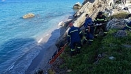 Firefighters retrieve the body of a migrant from the beach after a shipwreck on the island of Rhodes, southeastern Greece,…