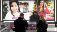 Cashier Druhan Parker, center, works behind a plexiglass shield Thursday, Nov. 19, 2020, as he checks out shoppers at an Ulta…