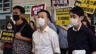 Pro-democracy lawmakers, from left; Eddie Chu, Raymond Chan and Ted Hui walk with supporters at a local court in Hong Kong…