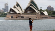 A man films the harbour foreshore on his mobile phone ahead of New Years Eve in Sydney, Australia, Thursday, Dec. 31, 2020. One…