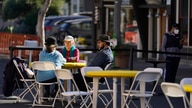 People sit at tables on a street closed off for outdoor dining Friday, Dec. 4, 2020, in Sausalito, Calif. The health officers…