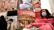"Residents wearing masks past by a screen showing a trailer for the film ""Days and Nights in Wuhan"" outside a mall in Wuhan in…"