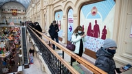 People stand in a queue to get a shot of Russia's Sputnik V coronavirus vaccine in a vaccination center in GUM State Department…