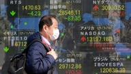 A man walks by an electronic stock board of a securities firm in Tokyo, Wednesday, Jan. 20, 2021. Asian shares were mostly…