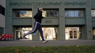 FILE — In his Dec. 18, 2020 file photo a runner passes the office of the California Employment Development Department in…