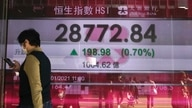 A woman walks past a bank's electronic board showing the Hong Kong share index at Hong Kong Stock Exchange Monday, Jan. 18,…