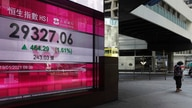 A woman walks past a bank's electronic board showing the Hong Kong share index at Hong Kong Stock Exchange in Hong Kong Tuesday…