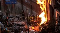 Fire-fighters carry a dead body next to a damaged building at Toledo Street following an explosion in downtown Madrid, Spain,…